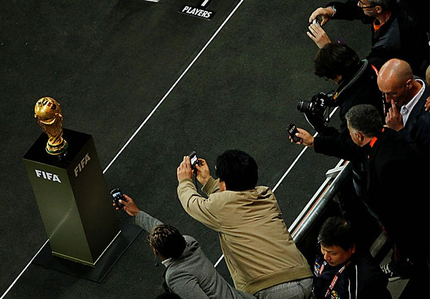 Spectators take photographs of the World Cup trophy at half-time during the World Cup final soccer match between the Netherlands and Spain at Soccer City in Johannesburg, South Africa, Sunday, July 11, 2010. (AP Photo/Themba Hadebe)