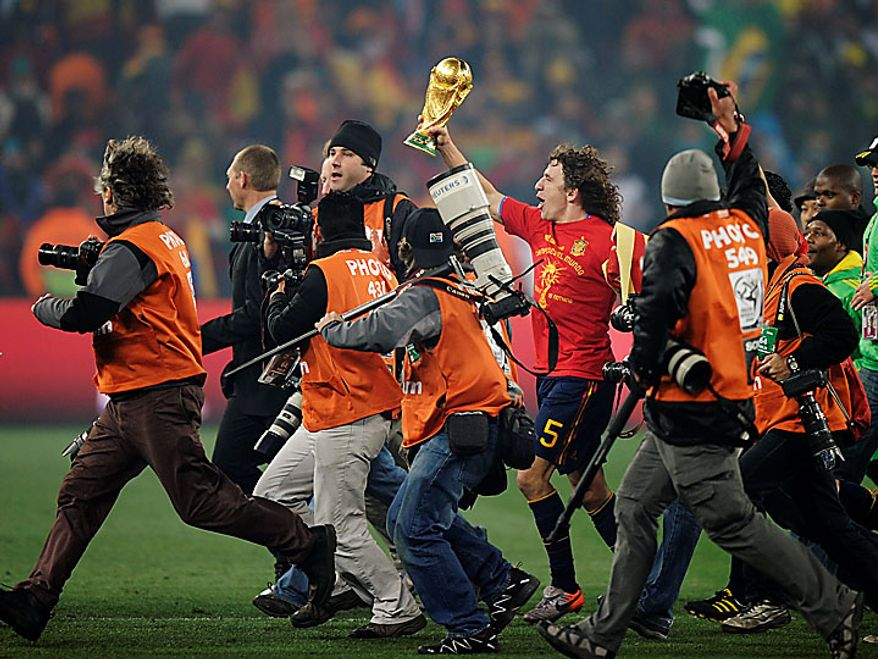 Spain's Carles Puyol, center, holds up the World Cup trophy as photographers surround him during the World Cup final soccer match between the Netherlands and Spain at Soccer City in Johannesburg, South Africa, Sunday, July 11, 2010. (AP Photo/Martin Meissner)