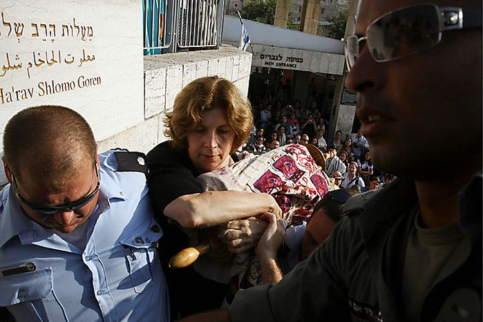 Anat Hoffman, center, chairwoman of the Women of the Wall organization, holds on to a Torah scroll as Israeli police attempt to take it from her and detain her outside the Western Wall, Judaism's holiest site, Monday, July 12, 2010. Ms. Hoffman was arrested for carrying a biblical scroll at Judaism's holiest site on Monday, in contravention of an Israeli high court ruling that bars women from carrying the holy texts in the area of the Western Wall, said police spokesman Micky Rosenfeld. (AP Photo/Tara Todras-Whitehill)