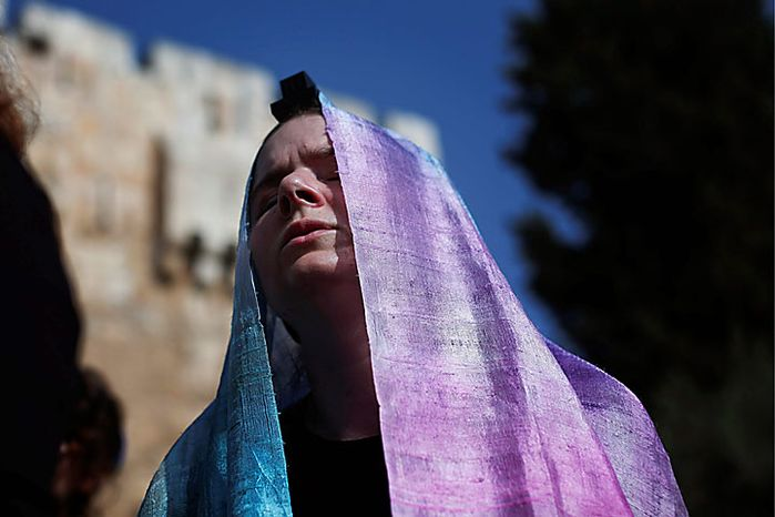 An Israeli member of the Women of the Wall organization prays outside a police station after Anat Hoffman, not pictured, the chairwoman for their organization, was detained outside the Western Wall, Judaism's holiest site, in Jerusalem's Old City, Monday, July 12, 2010. Ms. Hoffman was arrested for carrying a biblical scroll at a Judaism's holiest site on Monday in contravention of an Israeli high court ruling that bars women from carrying the holy texts in the area of the Western Wall, said police spokesman Micky Rosenfeld. (AP Photo/Tara Todras-Whitehill)