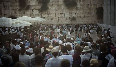 Israeli and international members of the Women of the Wall organization are seen through a screen as they pray at the Western Wall, Judaism's holiest site, in Jerusalem's Old City, Monday, July 12, 2010. Anat Hoffman, the chairwoman of the Women of the Wall, was arrested for carrying a biblical scroll at a Judaism's holiest site on Monday in contravention of an Israeli high court ruling that bars women from carrying the holy texts in the area of the Western Wall, said police spokesman Micky Rosenfeld. (AP Photo/Tara Todras-Whitehill)