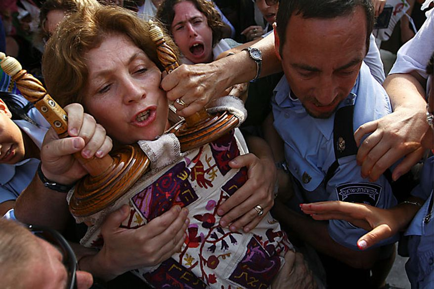 Anat Hoffman, left, chairwoman of the Women of the Wall organization, holds on to a Torah scroll as Israeli police attempt to take it from her and detain her outside the Western Wall, Judaism's holiest site, Monday, July 12, 2010. Ms. Hoffman was arrested for carrying a biblical scroll at a Judiasm's holiest site on Monday in contravention of an Israeli high court ruling that bars women from carrying the holy texts in the area of the Western Wall, said police spokesman Micky Rosenfeld. (AP Photo/Tara Todras-Whitehill)