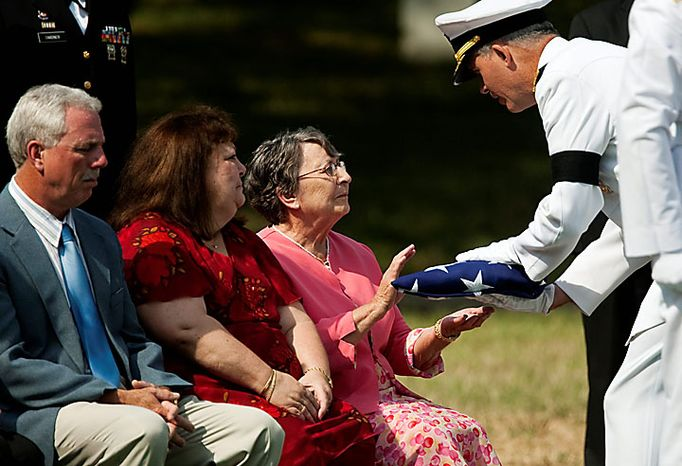 Mary Parker, Ensign Robert Langwell's aunt, receives a flag from Rear Adm. Jim Shannonto during the burial service for Langwell in Section 40 of Arlington National Cemetery in Arlington on Monday, July 12, 2010. Langwell was one of two sailors missing after the USS Magpie struck a mine off the coast of Chuksan-ri, South Korea, on Oct. 1, 1950. (AP Photo/Drew Angerer)