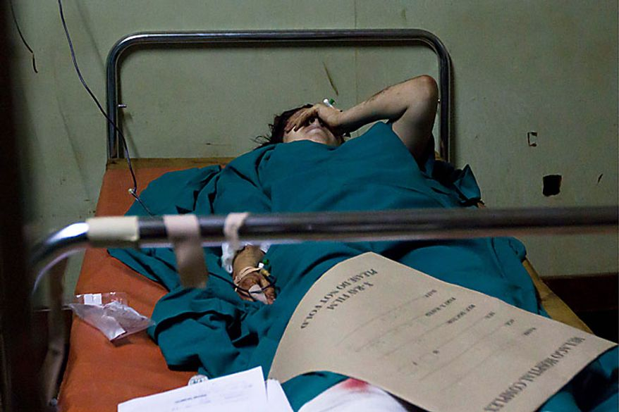 An American women lies injured at the emergency ward at the Mulago hospital, Monday, July 12, 2010, in Kampala after bombs exploded at two sites in Uganda's capital late Sunday as people watched the World Cup soccer final on TV, killing scores of people. (AP Photo/Marc Hofer)