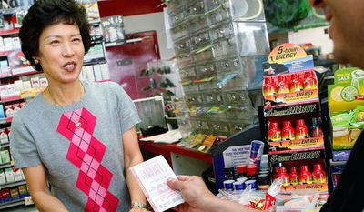 Sun Bae sells a chance for riches to Frank Gutierrez at the Times Market, where Bishop, Texas, native Joan Ginther bought two of her winning lottery tickets. (Associated Press)