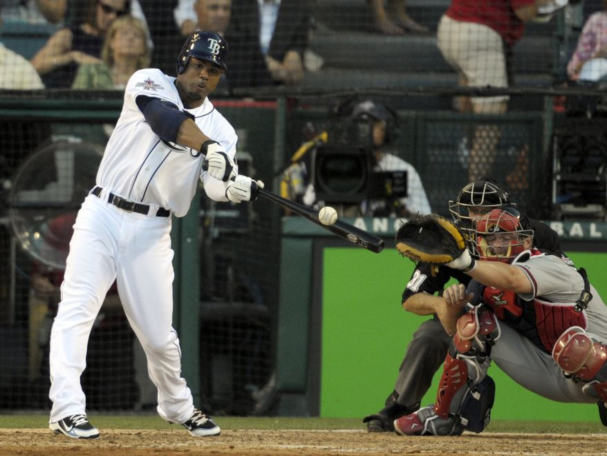 ASSOCIATED PRESS The American League's Carl Crawford, of the Tampa Bay Rays, hits into a fielder's choice during the fifth inning of the All-Star baseball game Tuesday, July 13, 2010, in Anaheim, Calif. National League catcher Brian McCann, of the Atlanta Braves, is at right.