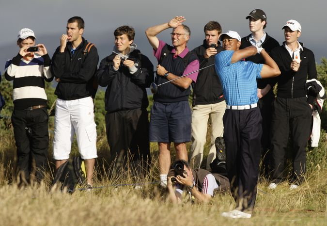 Spectators look on as Tiger Woods plays a shot on the 9th hole during a practice round on the Old Course at St. Andrews, Scotland, Tuesday, July 13, 2010. The British Open golf tournament begins at St. Andrews on Thursday, July 15. (AP Photo/Jon Super)
