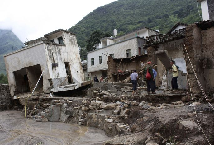 In this photo taken Tuesday, July 13, 2010, people gather around damaged houses after the flooding in Xiaohe, southwest China's Yunnan Province. Landslides slammed into three mountain hamlets in western China early Tuesday, killing 17 people and leaving 44 missing, while crews drained a fast-rising reservoir in another part of the country following heavy rains. The landslides swept through three different areas before dawn, state media said. In the worst-hit town of Xiaohe in Yunnan province, four died and rescuers were searching for 42 others, the official provincial newspaper Yunnan Daily reported on its website. (AP Photo/Xinhua)