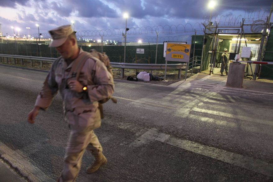 In this May 13, 2009, file photo, reviewed by the U.S. military, a U.S. trooper walks near an entrance to the Guantanamo detention facility at dawn, at Guantanamo Bay U.S. Naval Base, Cuba. (AP Photo/Brennan Linsley)