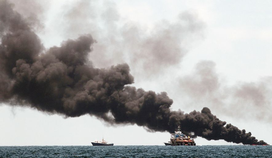 Vessels monitor oil burning near the Deepwater Horizon spill on Tuesday. BP officials placed a containment cap over the leak, hoping the oil flow will slow, and said BP will begin gradual tests to see if the cap can stop oil from spewing into the sea. (Associated Press)