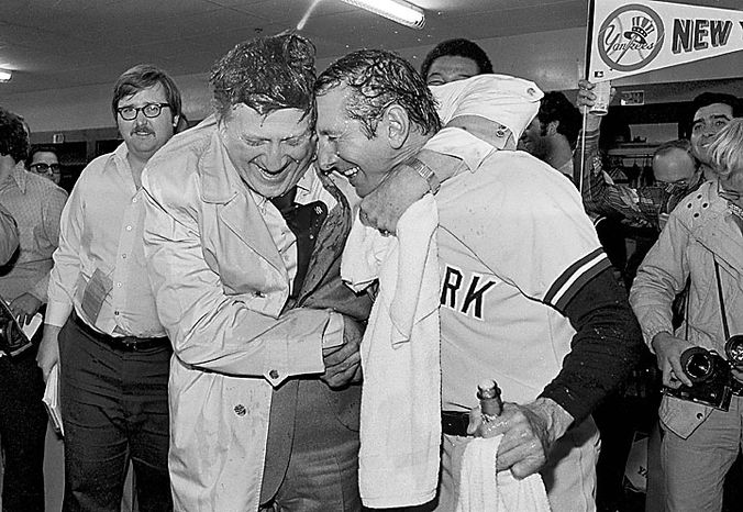 This Oct. 9, 1977, file photo shows George Steinbrenner (left), principal owner of the New York Yankees, giving Manager Billy Martin a bearhug and congratulations after each was doused by champagne in a dressing room at Royals Stadium after the Yankees defeated the Kansas City Royals, 5-3, to take the AL championship. Steinbrenner, who rebuilt the Yankees into a sports empire with a mix of bluster and bi