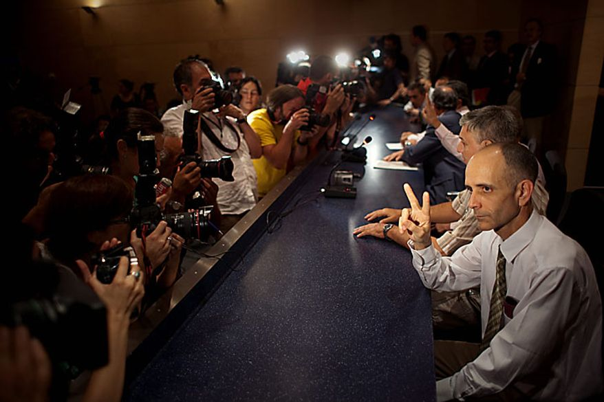 Cuban dissident Jose Luis Garcia gestures for press photographers during a media conference upon  arrival at Madrid's Barajas airport on Tuesday, July 13, 2010. Seven Cuban political prisoners and members of their families arrived in Madrid on Tuesday, the first of a group of inmates the government in Havana has promised to release, an official said. It was the start of a mass liberation of dissidents promised by Cuba. (AP Photo/Emilio Morenatti)