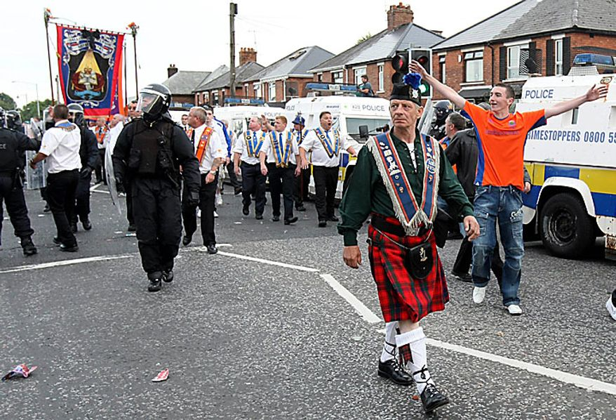 A Orange Order march is escorted by Police Service of Northern Ireland officers past the Ardoyne Area of north Belfast, Northern Ireland, Monday, July 12, 2010. Police battled Irish nationalists for control of a Belfast road Monday as a day dominated by peaceful Protestant parades across Northern Ireland turned violent when night fell. (AP Photo)