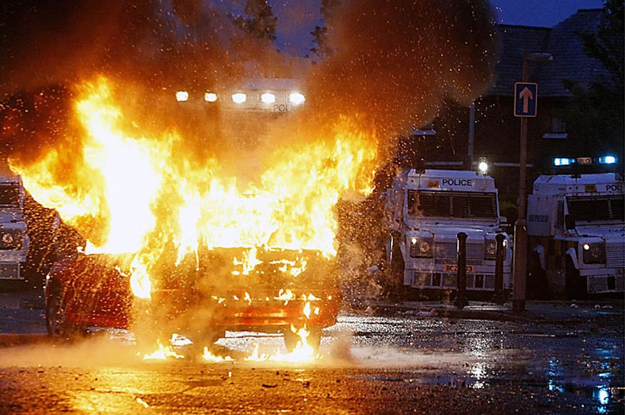 A car explodes in front of a line of police cars as nationalist protesters clash with police in Belfast, Northern Ireland, late Monday, July 12, 2010. Police struggled Monday overnight until early Tuesday to quell rioting by Irish Catholic nationalists in several parts of Northern Ireland following a day of mass Protestant parades, an annual event that often pushes sectarian animosity past boiling point. (AP Photo / Niall Carson, PA)