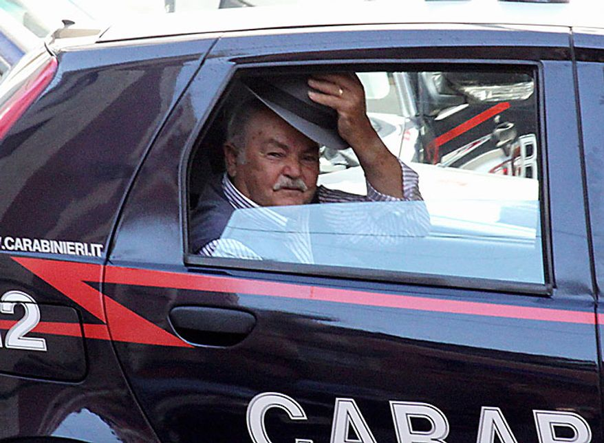 An unidentified man doffs his hat as he rides in a Carabinieri (paramilitary police) car after being arrested in Reggio Calabria in southern Italy on Tuesday, July 13, 2010, following one of the biggest operations ever against the powerful 'ndrangheta crime organization, in which 300 people were arrested, including top bosses, and million of dollars in property seized. The pre-dawn raids Tuesday involved some 3,000 police across the country. Charges include murder, extortion, arms and drug trafficking, and criminal association. Investigators described the operation as one of biggest blows ever to an organization that today is considered more powerful than the Sicilian Mafia. (AP Photo/Adriana Sapone)