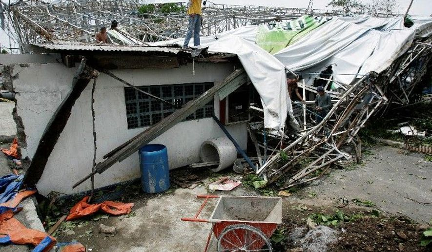 Philippines workers try to arrange a tarpaulin Wednesday from a billboard that collapsed on top of a house south of Manila due to strong winds from Typhoon Conson. (Associated Press)