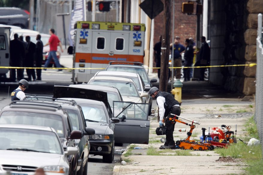 Authorities search a car for a suspected bomb near a railroad overpass in Newark, N.J., on Wednesday, July 14, 2010. A mechanical robot and the red gas cans it removed from the car sit nearby. (AP Photo/Mel Evans)