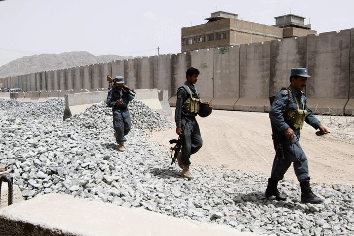 Afghan policemen secure a police base that came under attack Tuesday night in Kandahar, south of Kabul, Afghanistan. (AP Photo/Allauddin Khan)