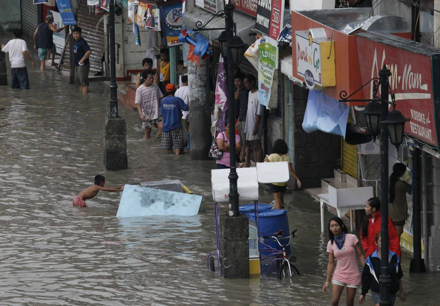 Residents wade through a flooded street at Las Pinas, south of Manila, on Wednesday, July 14, 2010, hours after typhoon Conson lashed through Manila and other provinces in the Philippines. The first typhoon to lash the Philippines this year has toppled trees and power lines, causing widespread blackouts, canceling flights, classes and suspending work in some government offices. (AP Photo/Bullit Marquez)