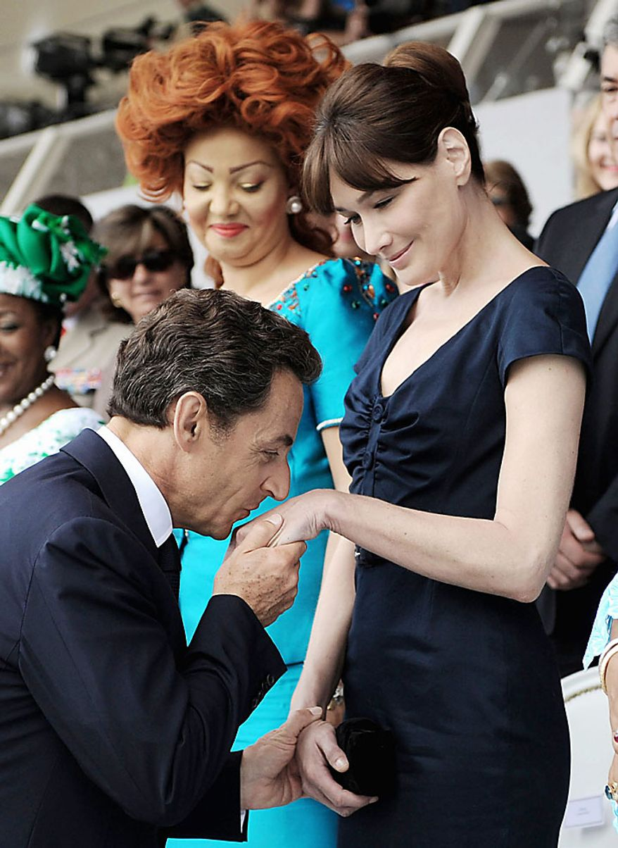 With Cameroonian first lady Chantal Biya (left) looking on, French President Nicolas Sarkozy kisses the hand of his wife, Carla Bruni-Sarkozy, during the annual Bastille Day military parade in Paris on Wednesday, July 14, 2010. (AP Photo/Eric Feferberg, Pool)
