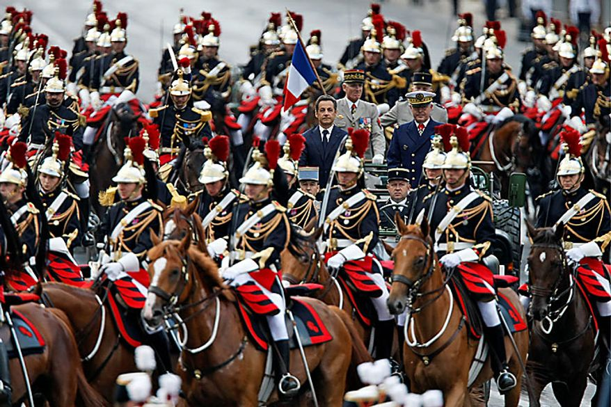 French President Nicolas Sarkozy (center left) and Chief of Staff Adm. Edouard Guillaud (center right) ride in the command car amid French Republican Horse Guards during the annual Bastille Day military parade on the Avenue des Champs-Elysees in Paris on Wednesday, July 14, 2010. (AP Photo/Francois Mori)
