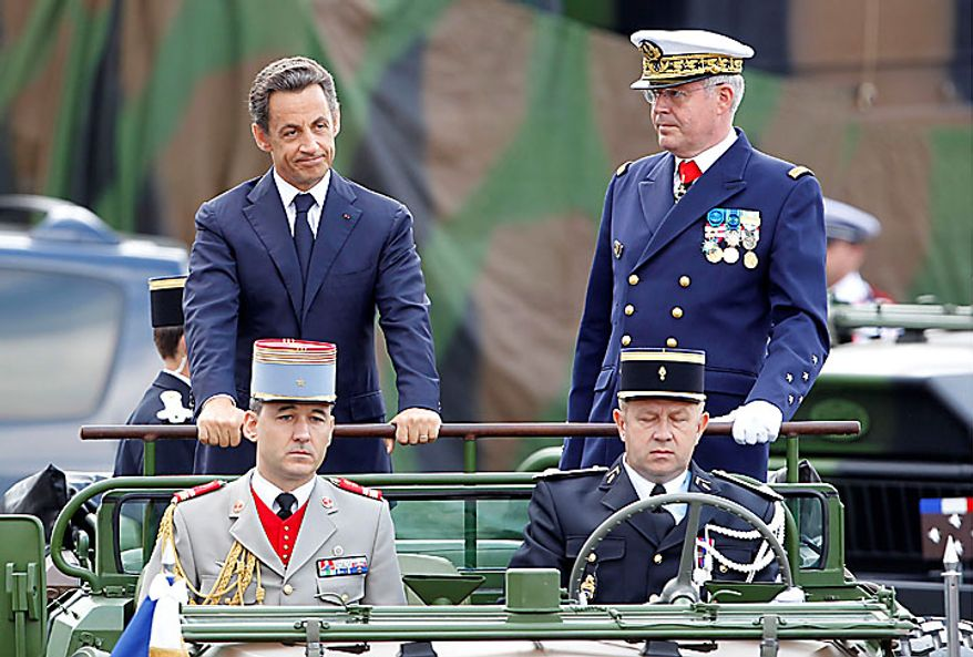 French President Nicolas Sarkozy (left) stands in his command car with Chief of Staff Adm. Edouard Guillaud (standing at right) during Bastille Day ceremonies in Paris on Wednesday, July 14, 2010. Thirteen African countries were invited to the ceremonies. (AP Photo/Laurent Cipriani)
