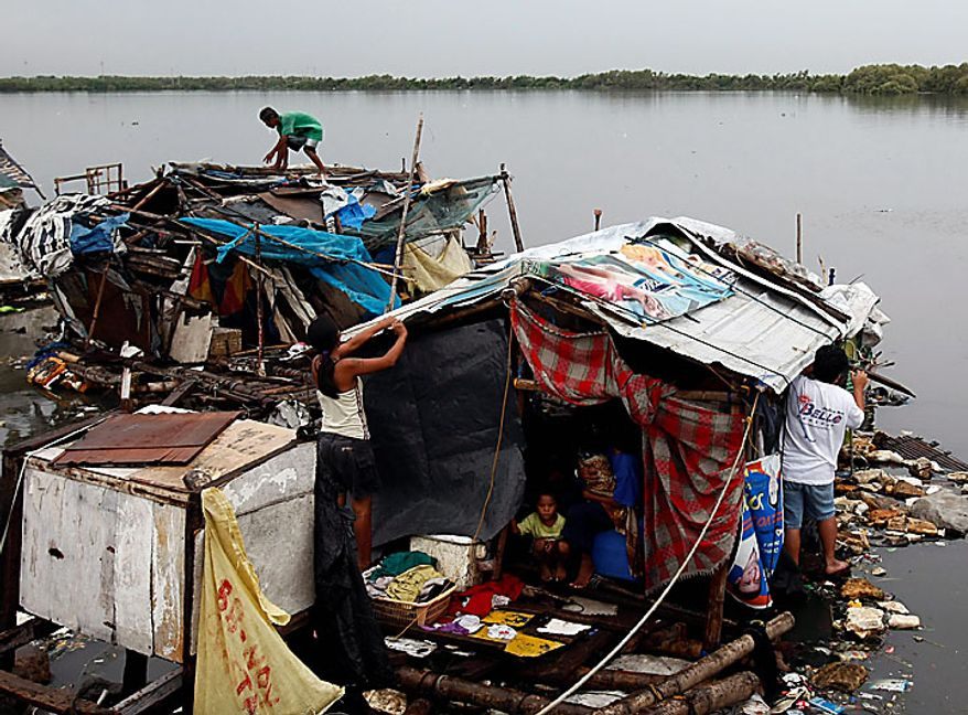 Residents fix their shanties along a coastal road after typhoon Conson hit Las Pinas, Philippines, south of Manila, on Wednesday, July 14, 2010. The Philippines' first typhoon of the year prompted flight and ferry cancellations, school closures, and warnings of floods and landslides. AP Photo/Bullit Marquez)