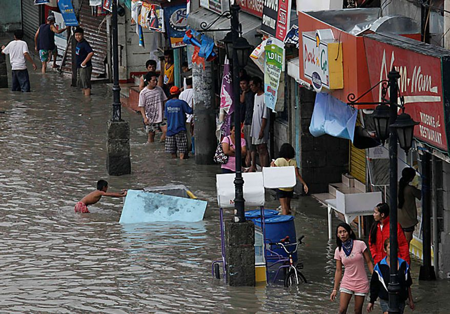 Residents wade through a flooded street in Las Pinas, Philippines, south of Manila, on Wednesday, July 14, 2010, hours after typhoon Conson lashed the Manila area and other provinces. The Philippines' first typhoon of the year prompted flight and ferry cancellations, school closures, and warnings of floods and landslides. (AP Photo/Bullit Marquez)