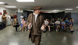"""ASSOCIATED PRESS PHOTOGRAPHS Tim Fairfield wears period clothing as he talks to children about the merits of free enterprise on the first night of a Vacation Liberty School in Georgetown, Ky., on Monday. """"If we're going to take our country back, we've got to remember where we came from - not only as adults, but we need to teach our children,"""" said Mr. Fairfield, one of the teachers."""