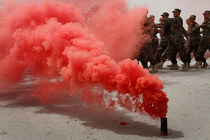 Recruited Afghan soldiers march through a colored fog bomb after taking an oath during a ceremony at the Ghazi Military Training Center, where they are being trained by Turkish military officers of the NATO-led International Security Assistance Force (ISAF) in Kabul, Afghanistan, on Thursday, July 15, 2010. (AP Photo/Musadeq Sadeq)
