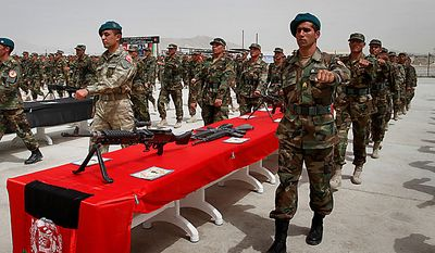 Recruited Afghan soldiers march for an oath-taking ceremony with a Turkish military officer, front center, at the Ghazi Military Training Center, where they are being trained by Turkish military officers of the NATO-led International Security Assistance Force (ISAF) in Kabul, Afghanistan, on Thursday, July 15, 2010. (AP Photo/Musadeq Sadeq)