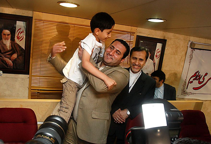 Shahram Amiri, center, an Iranian nuclear scientist who disappeared a year ago, holds his 7-year-old son Amir Hossein at the conclusion of his news briefing as he arrived at the Imam Khomeini airport just outside Tehran, Iran, Thursday, July 15, 2010. Mr. Amiri claimed Thursday he suffered extreme mental and physical torture at the hands of U.S. interrogators after disappearing last year, adding to Tehran's allegations he was abducted by American agents. (AP Photo/Vahid Salemi)