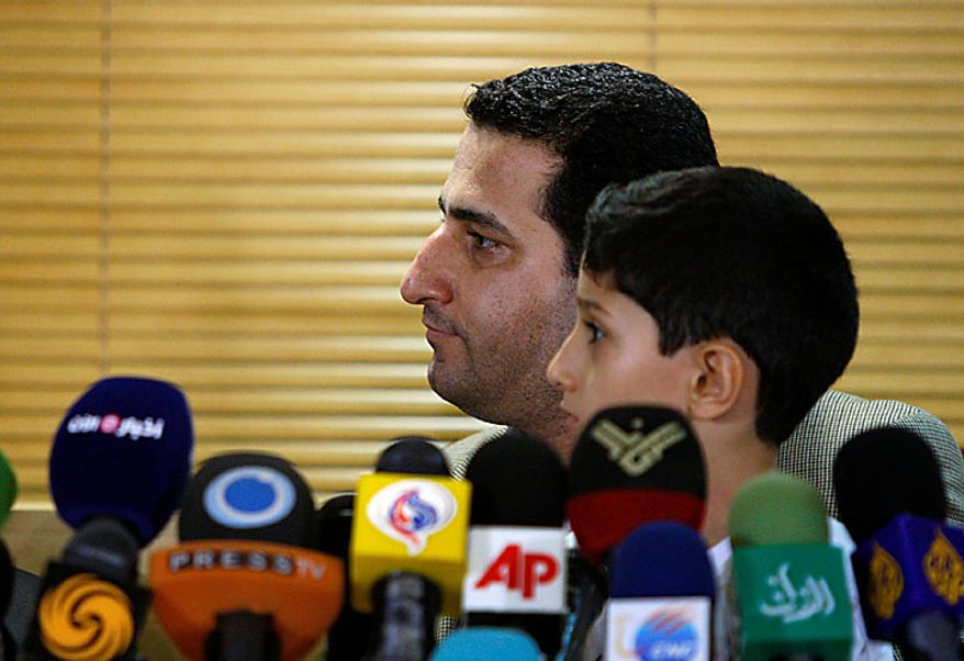 Shahram Amiri, an Iranian nuclear scientist who disappeared a year ago, listens to a question while holding his 7-year-old son Amir Hossein during a news briefing as he arrives at the Imam Khomeini airport just outside Tehran, Iran, Thursday, July 15, 2010. Mr. Amiri claimed Thursday he suffered extreme mental and physical torture at the hands of U.S. interrogators after disappearing last year, adding to Tehran's allegations he was abducted by American agents. (AP Photo/Vahid Salemi)