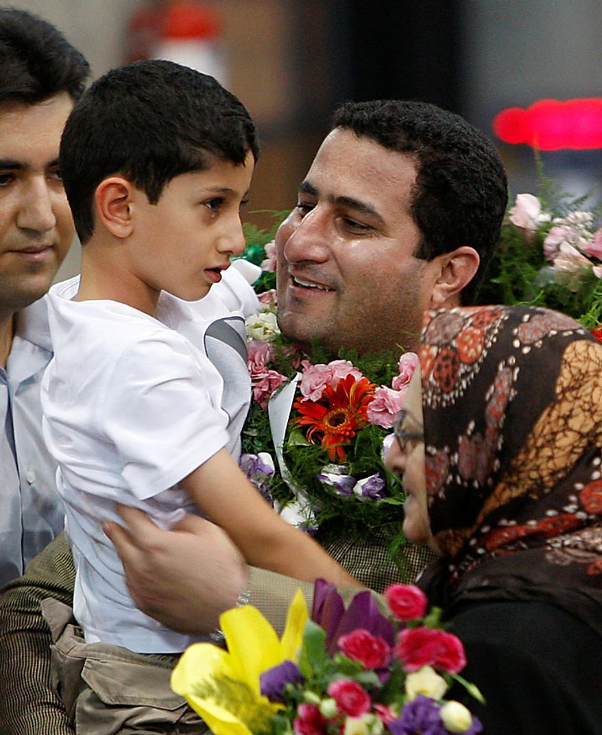 Shahram Amiri, an Iranian nuclear scientist who disappeared a year ago, holds his son, Amir Hossein, as he arrives at the Imam Khomeini airport just outside Tehran, Iran, Thursday, July 15, 2010. Mr. Amiri claimed Thursday he suffered extreme mental and physical torture at the hands of U.S. interrogators after disappearing last year, adding to Tehran's allegations he was abducted by American agents. (AP Photo/Vahid Salemi)