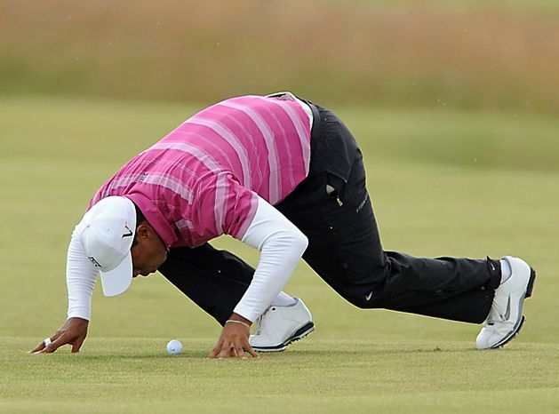 American Tiger Woods does a press up over his ball on the 14th fairway on the first day of the Open championship in St. Andrews, Scotland on July 15, 2010. (UPI/Hugo Philpott)