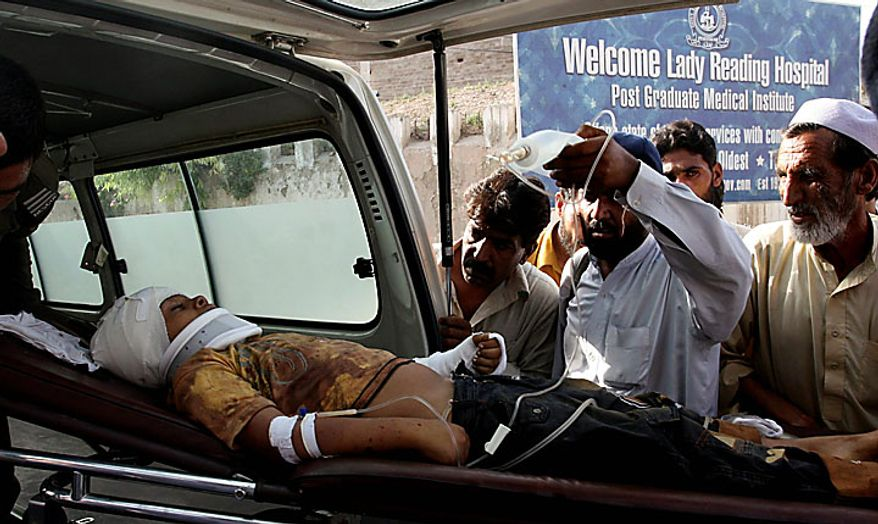 People look at a boy injured in a suicide attack, arrives at a local hospital in Peshawar, Pakistan on Thursday, July 15, 2010. An apparent suicide bombing near a bus terminal in Pakistan's Swat Valley killed five people and wounded at least 58 on Thursday, officials said, a sign that Islamist militants remain active in the northwest region despite a massive army operation.(AP Photo/Mohammad Sajjad)