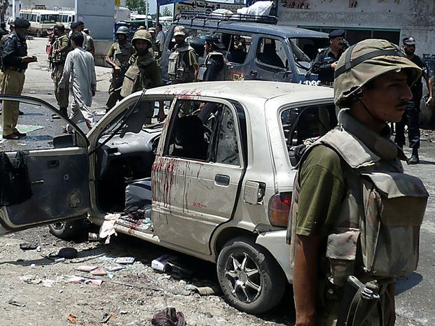 Pakistani soldiers and police officers guard the site of an apparent suicide bombing in Mingora, capital of Pakistan's troubled Swat valley on Thursday, July 15, 2010. The apparent suicide bombing near a bus terminal in Pakistan's Swat Valley killed three people and wounded at least 35 people Thursday, officials said, a sign that Islamist militants remain active in the northwest region despite a massive army operation against them.  (AP Photo/Naveed Ali)