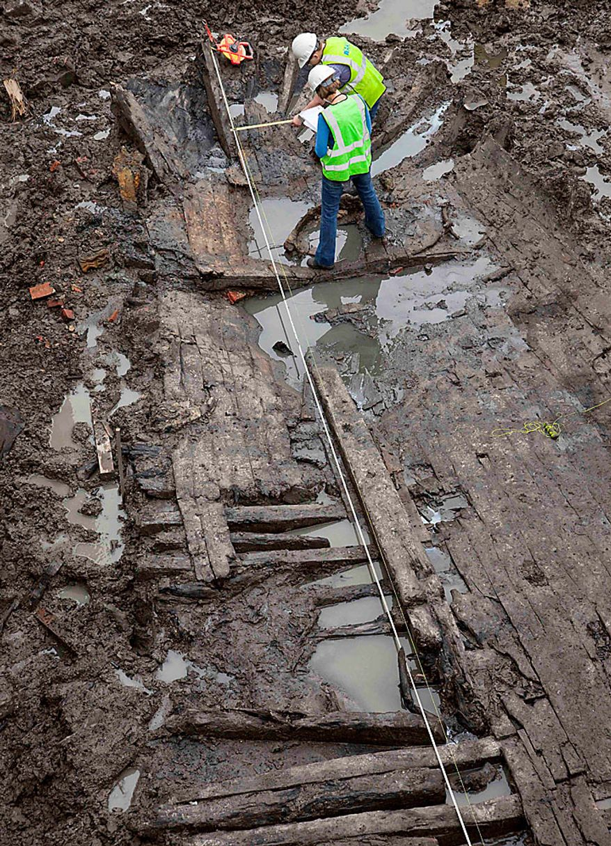 Archeologists Elizabeth Meade, top, and Molly McDonald take measurements of the wood hull of a 32-foot-long (9.75 meters) 18th century boat at the World Trade Center site on Thursday, July 15, 2010 in New York. (AP Photo/Mark Lennihan)