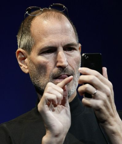 In this file photo taken June 7, 2010, Apple CEO Steve Jobs demonstrates the new iPhone 4 during the Apple Worldwide Developers Conference, in San Francisco. Apple Inc. is holding a press conference at its Silicon Valley headquarters Friday morning to talk about its latest iPhone model. (AP Photo/Paul Sakuma, File)