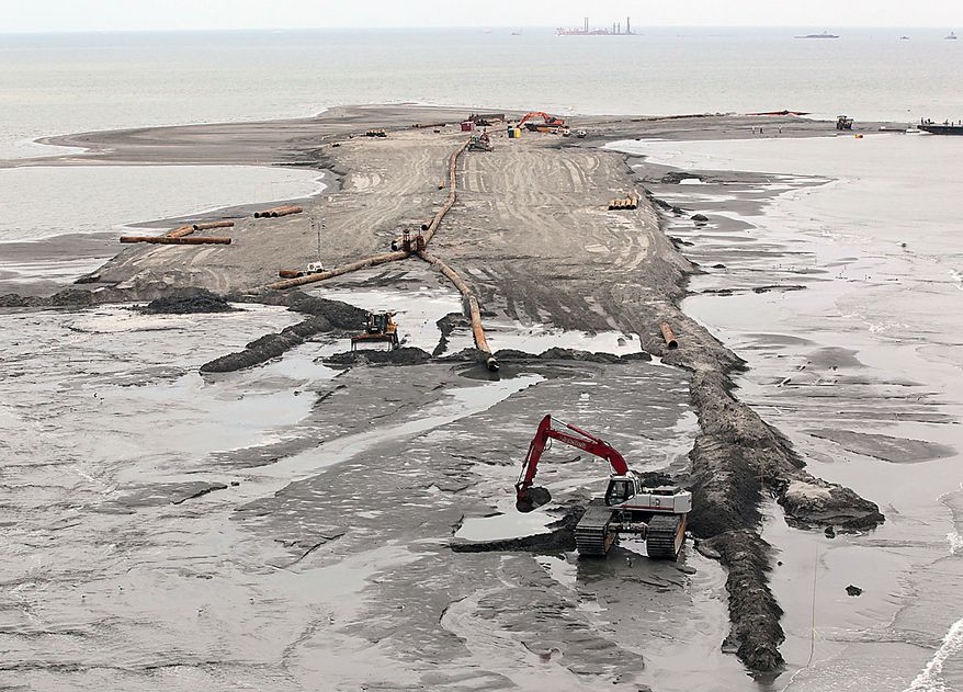 Workers continue to construct a berm system on the northern end of the Chandeleur Islands, La., Thursday, July 15, 2010. A tightly fitted cap was successfully keeping oil from gushing into the Gulf of Mexico for the first time in three months, BP said Thursday. (AP Photo/Dave Martin)