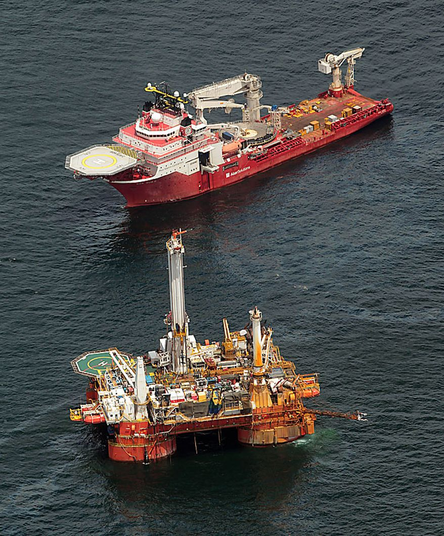 The Boa Sub C work boat, top, operates near the Q4000 drilling rig at the site of the Deepwater Horizon incident in the Gulf of Mexico Friday, July 16, 2010. The wellhead has been capped and BP is continuing to test the integrity of the well before resuming production. (AP Photo/Dave Martin)
