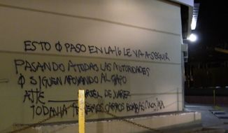"""**FILE** A wall at a shopping center is covered by graffiti that reads in Spanish: """"What happened on the 16 (street) is going to keep happening to all the authorities that continue to support the Chapo (Guzman), sincerely, the Juarez Cartel. We still have car bombs (expletive) ha ha."""" Cartel assailants laid a trap for federal police and attacked them with a car bomb on July 15, the first time a drug cartel have used explosives to attack Mexican security forces, marking an escalation in the country's drug war. (Associated Press)"""