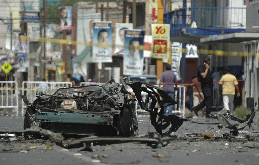 The remains of a vehicle are cordoned off in a street in the northern border city of Ciudad Juarez, Mexico, Friday July 16, 2010. Mexican investigators ran forensic tests to determine whether drug gangs used a car bomb in an attack on police patrol trucks that killed two officers and wounded nine people on Thursday. A car bomb would mark an unprecedented escalation of Mexico's drug war and confirm long-standing fears that the cartels are turning to explosives in their fight against security forces. (AP Photo)