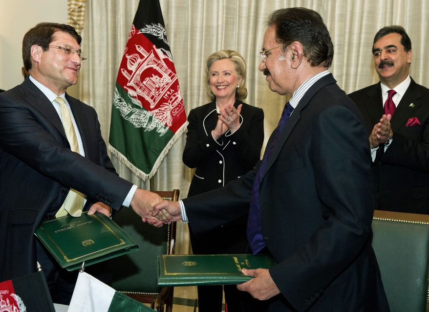 Associated Press Secretary of State Hillary Rodham Clinton and Pakistani Prime Minister Yusuf Raza Gilani (right) applaud the signing of a trade treaty between Pakistan and Afghanistan on Sunday. Mrs. Clinton traveled to Pakistan on Sunday, appealing for cooperation between the two countries.