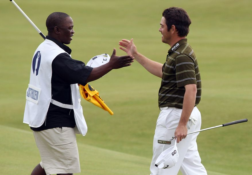 South Africa's Louis Oosthuizen (right) celebrates on the 18th green with his caddie, Zack Rasego, after winning the British Open golf championship on the Old Course at St. Andrews, Scotland, on Sunday, July 18, 2010. (AP Photo/Alastair Grant)