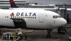 ** FILE ** In this file photo taken June 7, 2010, a Delta Airlines Inc. plane sits on the tarmac at Seattle-Tacoma International Airport in Seattle. Delta Air Lines reversed a second-quarter loss with with what it said Monday, July 19, is its largest quarterly profit in a decade thanks to strong passenger revenue. (AP Photo/Ted S. Warren, File)