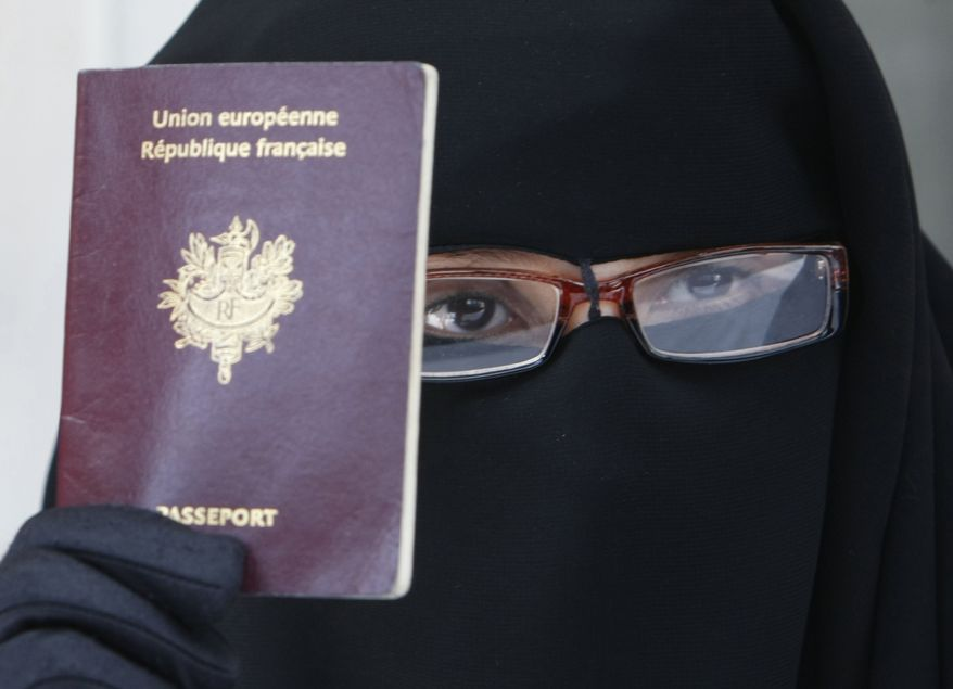 This May 18 2010, file photo shows a woman, who gave her name as Najat, holding her passport during a press conference in Montreuil, east of Paris. France's lower house of parliament overwhelmingly approved a ban on wearing burqa-style Islamic veils on July 13. On Sunday, July 18, 2010, Syria banned such face-covering veils on university campuses. (AP Photo/Remy de la Mauviniere, FILE)
