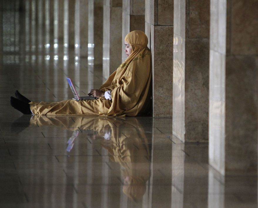 An Indonesian Muslim woman checks her laptop after an afternoon prayer at Istiqlal Mosque in Jakarta, Indonesia, Monday, July 19, 2010. People in the world's most populous Muslim nation have been facing Africa, not Mecca, while praying. Indonesia's highest Islamic body acknowledged Monday it made a mistake when issuing an edict in March saying the holy city in Saudi Arabia was to the country's west. (AP Photo/Irwin Fedriansyah)