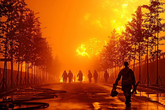Fire fighters walk near flames towering from a pipeline explosion at a Chinese port in Dalian in northern China's Liaoning province on Saturday, July 17, 2010. The oil pipeline at the busy Chinese port exploded, causing a massive fire that burned for 15 hours before being put out Saturday. Officials said no one was killed. (AP Photo)