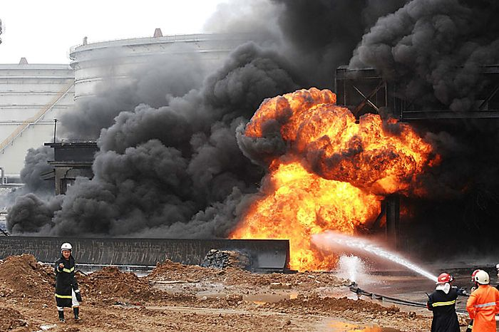 Fire fighters try to contain the flames from a pipeline explosion at a Chinese port in Dalian in northern China's Liaoning province on Saturday, July 17, 2010. The oil pipeline at the busy Chinese port exploded, causing a massive fire that burned for 15 hours before being put out Saturday. Officials said no one was killed. (AP Photo)
